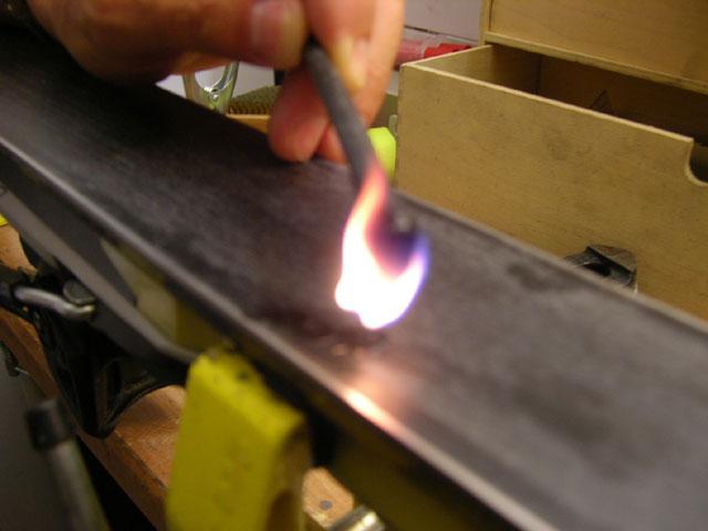 Поджигаем свечку и, держа ее над царапиной, как можно ближе к поверхности для прогрева пламенем пластика лыжи, капаем  с избытком на поврежденное место