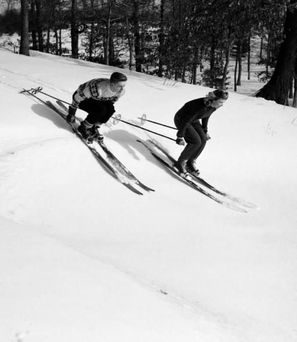 Молодая пара на лыжах мчитсявниз по склонув традиционных лыжных ботинках на шнуровке